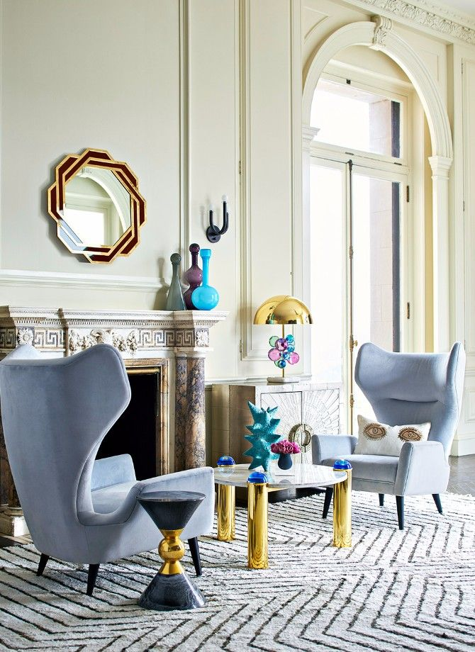 blue velvet chairs, white black patterned rug, white wall, marble fireplace, golden white round coffee table