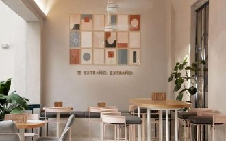 cafe, white marble floor, white wall, wooden table, grey stools, grey chairs