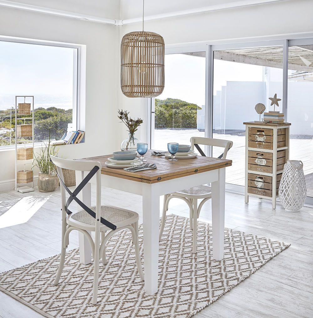dining room, white wooden floor, white wall, wooden table, white chairs, patterned rugs, rattan pendant