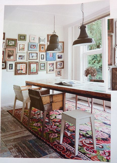 dining room, wooden floor, patterned rug, wooden table, wooden chair, white wall, black pendants