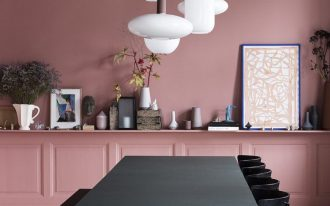 dining room, wooden floor, pink wall, pink wainscoting, floating shelves, white pendants, black dining table, black bench, black chairs