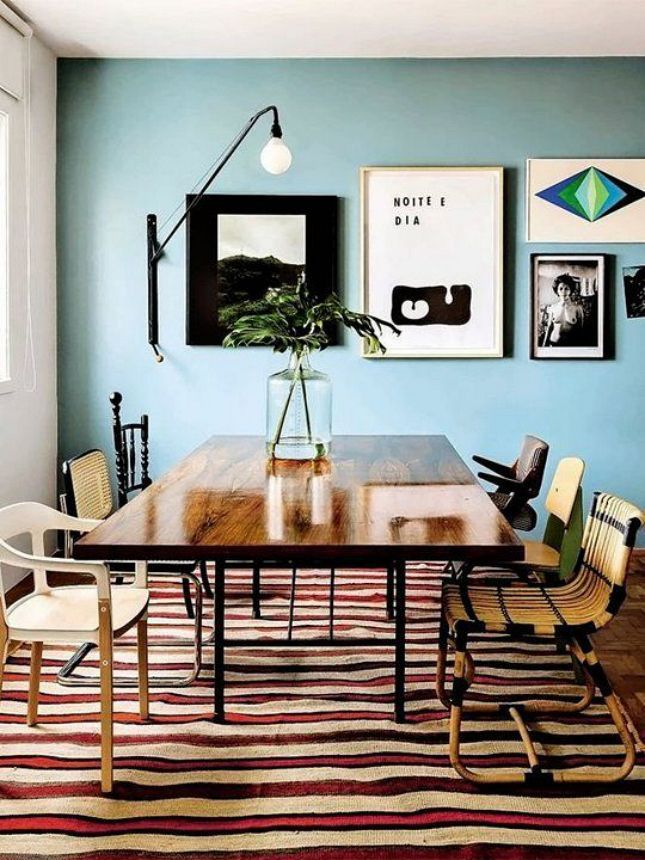 dining room, wooden floor, striped rug, bule wall, white wall, wooden dining table, rattan chair, wooden chair, black sconce