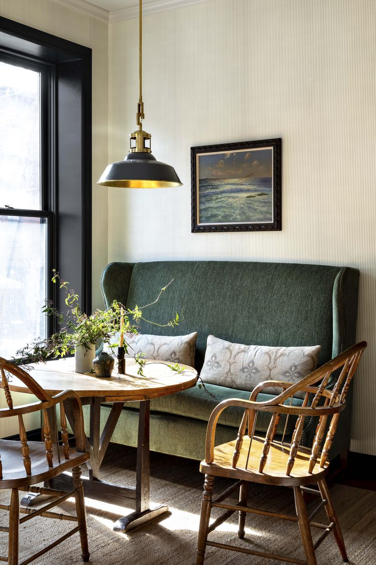 dining room, wooden floor, white wall ,green sofa, wooden chairs, wooden round table, green pendant