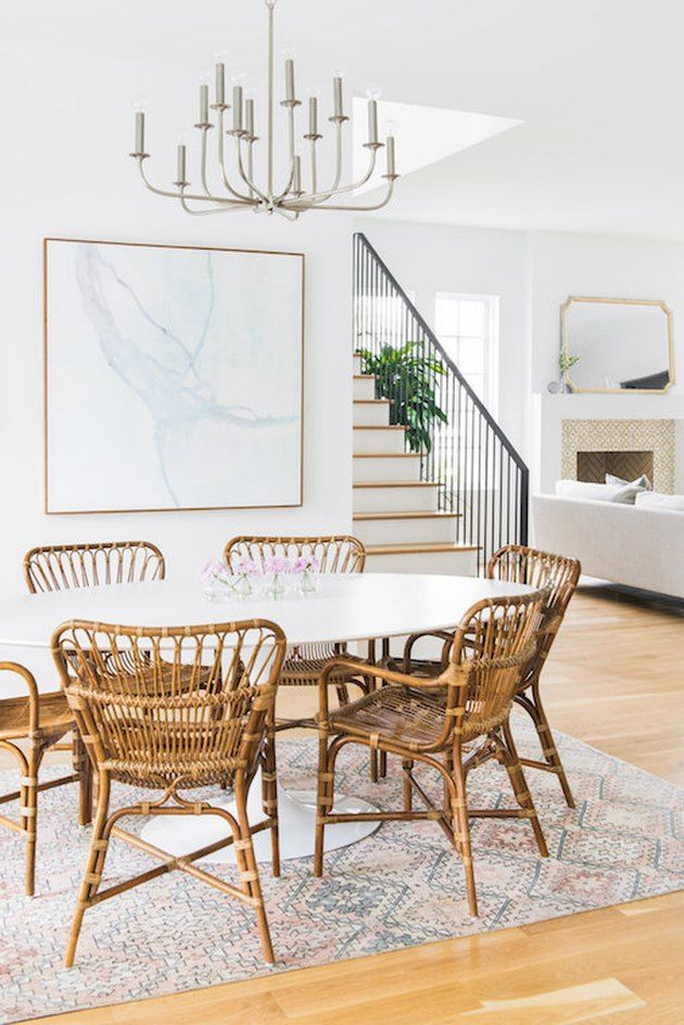dining room, wooden floor, white wall, white round dining table, bamboo chairs, chandelier, patterned rug