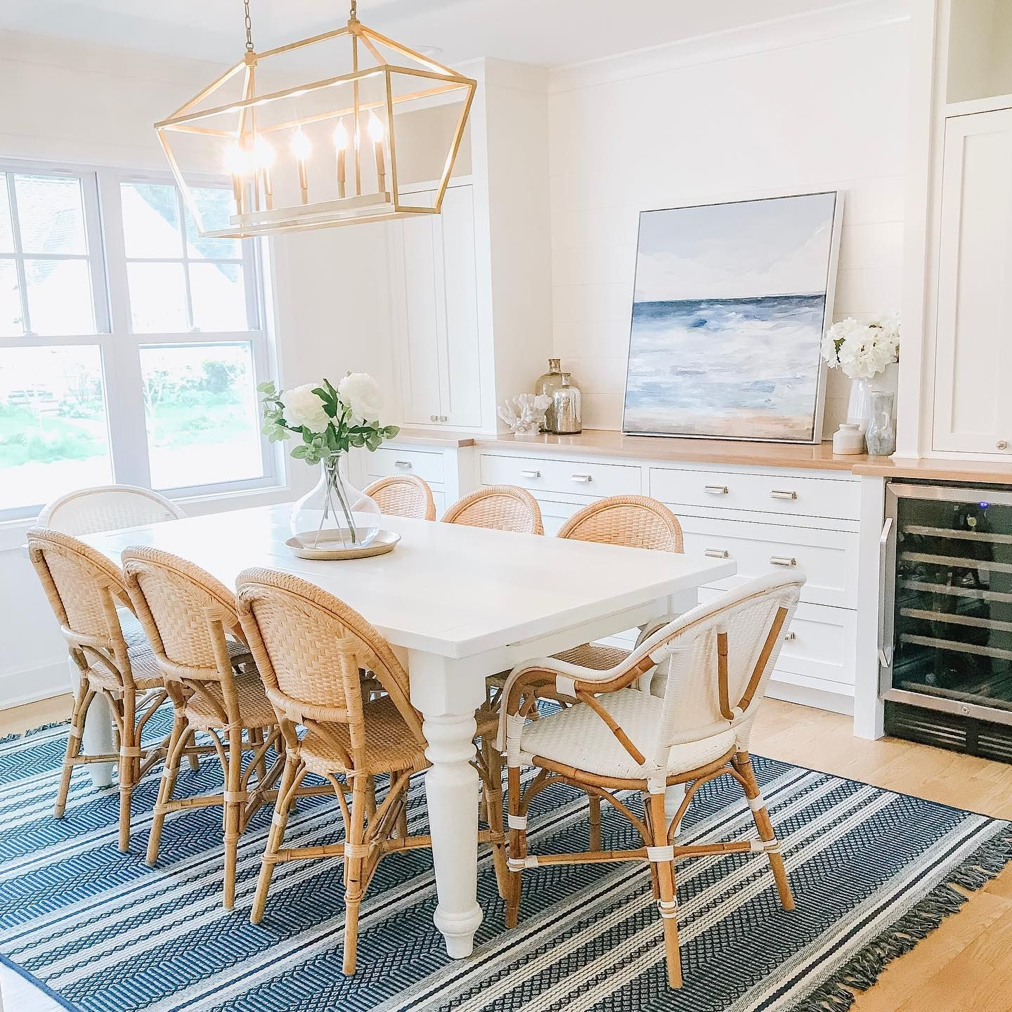 dining room, wooden floor, white wooden table, wooden chair with rattan seat, bamboo chair with white rattan, white cabinet, golden pendant
