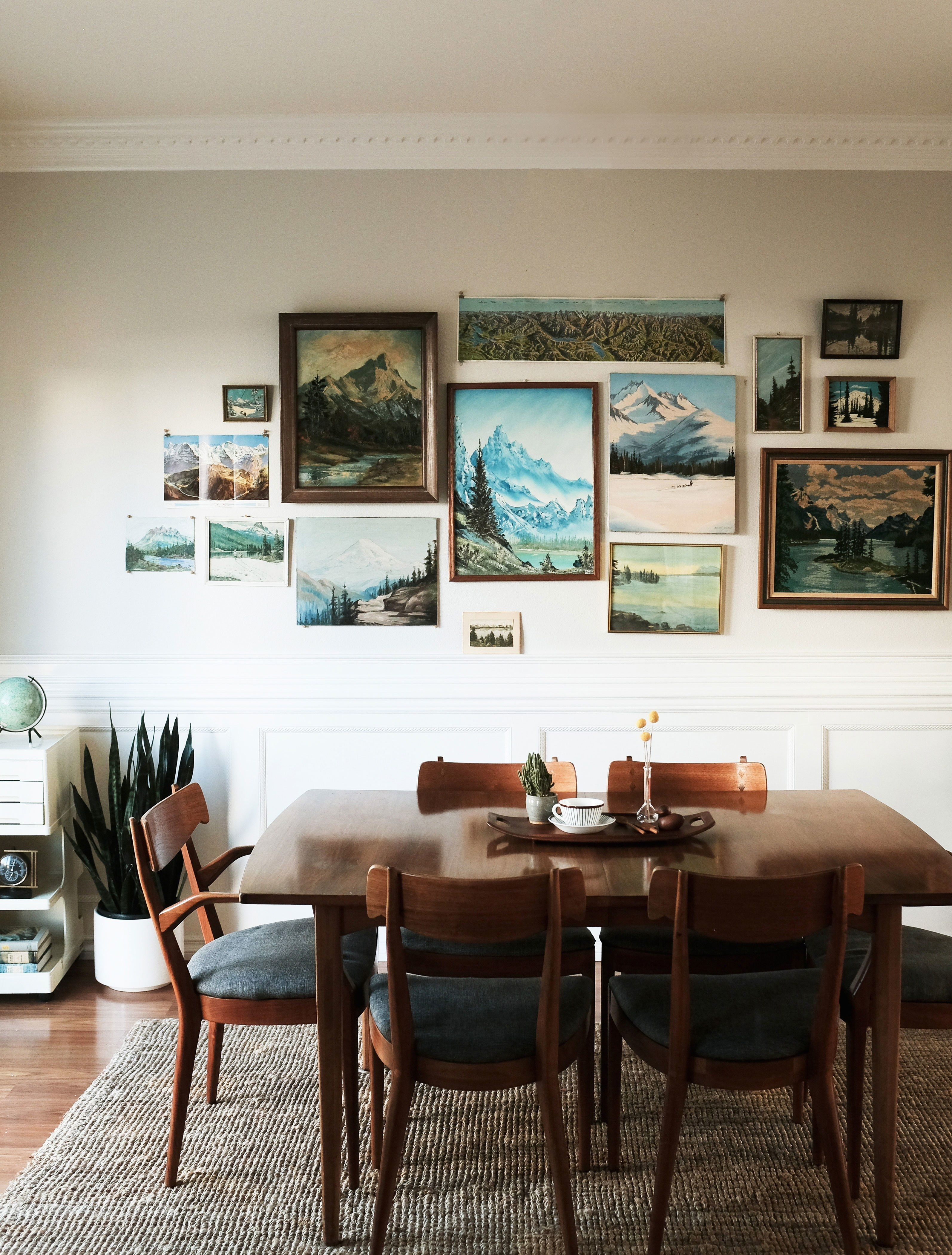 dining room, wooden table, wooden chairs with blue cushion, rattan rug, white wall, white cabinet