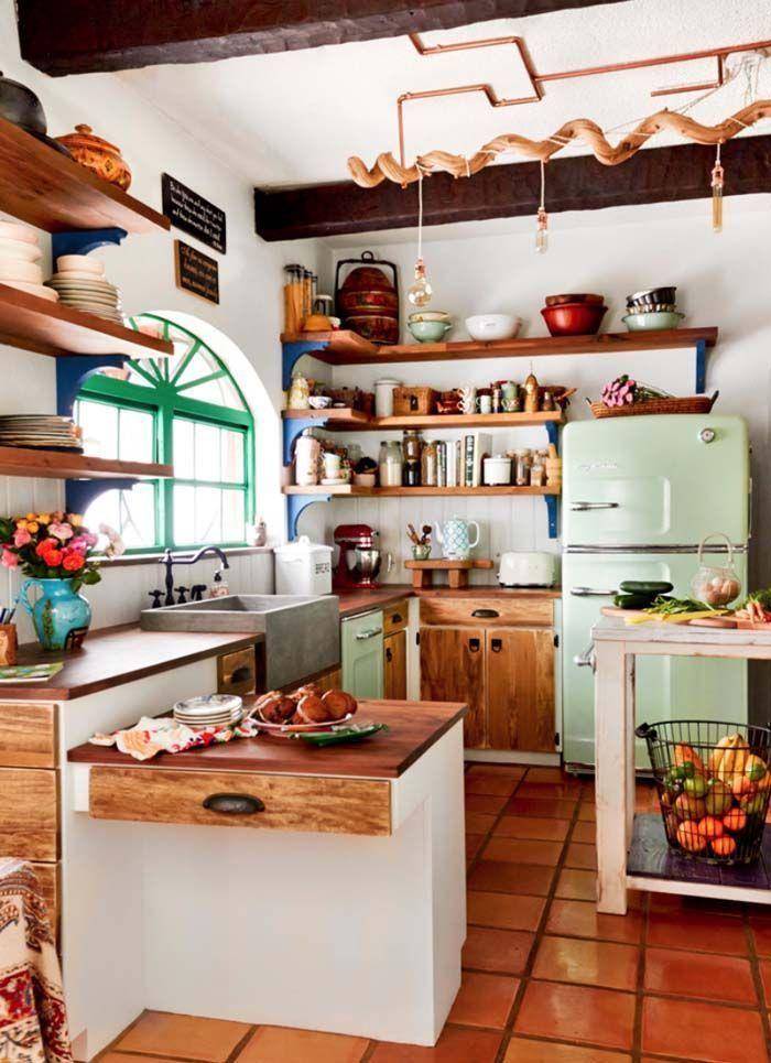 kitchen, brown floor tiles, white wall, white fridge, white wall tiles, wooden cabinet, wooden top, white wooden stool, green framed window, wooden floating shelves