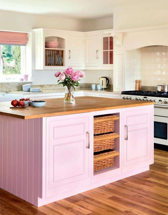 kitchen, wooden floor, pink wooden island cabinet, white wall, white nook for stove, marble top, window, white cabinet