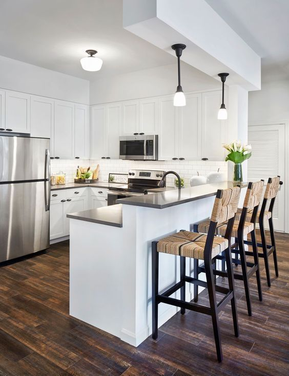 kitchen, wooden floor, white upper bottom cabinet, white island with black top, black wooden stools with rattan seats and back