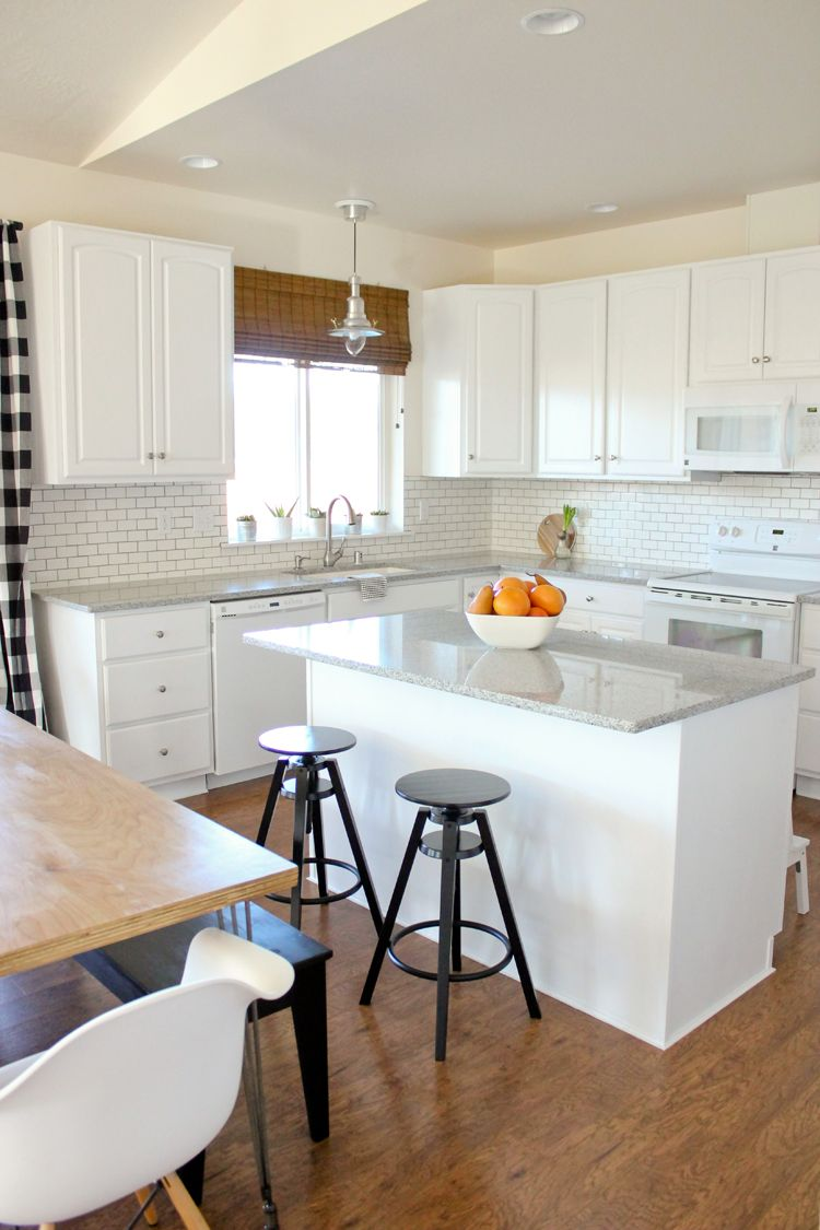 kitchen, wooden floor, white upper bottom cabinet, white subway tiles, white island, black stools