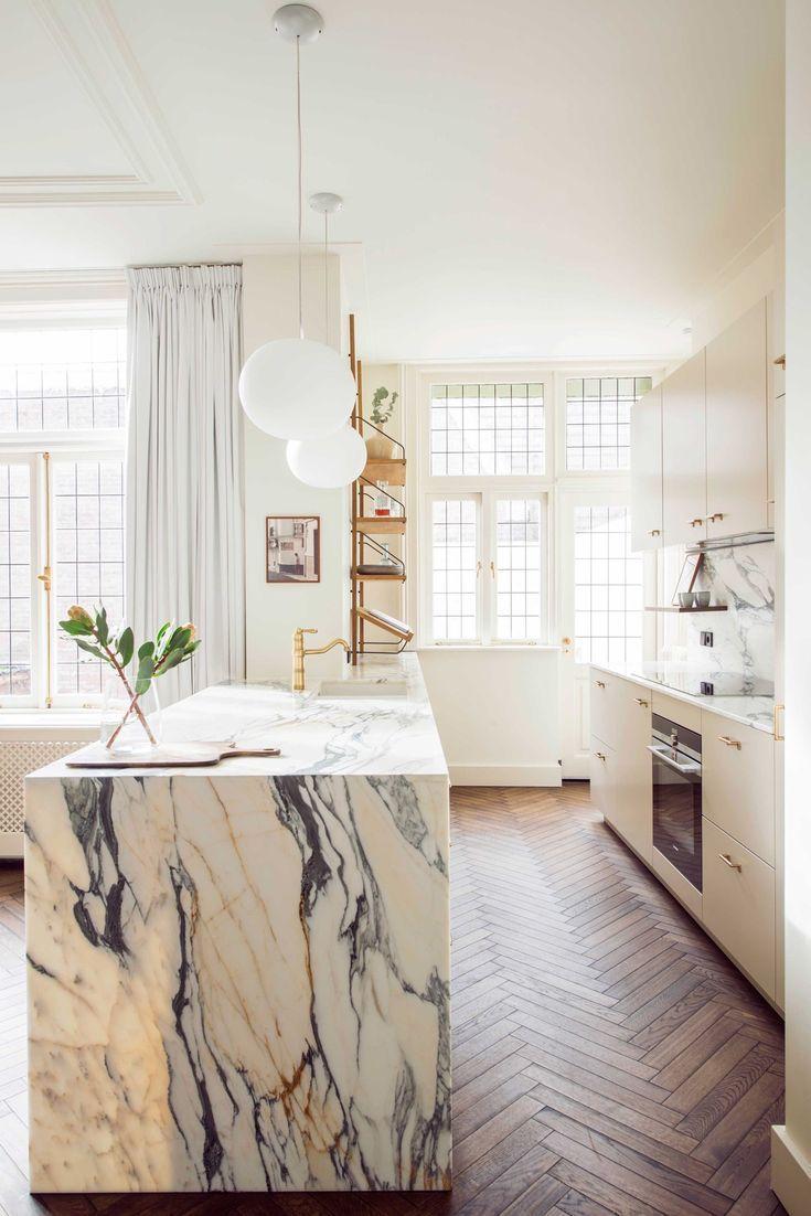 kitchen, wooden herringbone floor, white marble island, white cabinet, white wall, white pendants, shelves