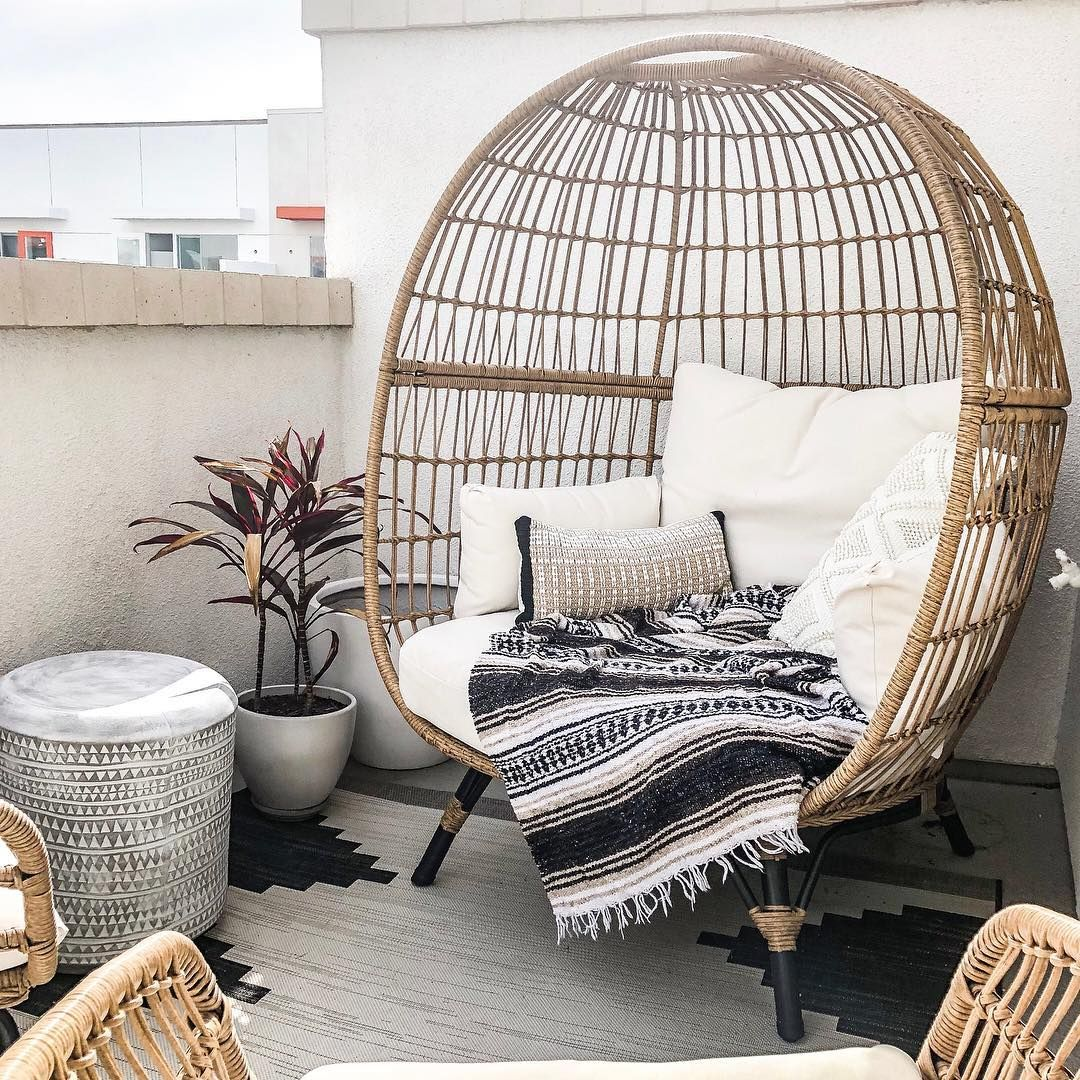 large rattan chair with white cushion and pillows, patterned rug, side table