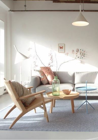 living room, gey rug, white wall, white sofa, wooden tray table, blue tray table, wooden rattan chair