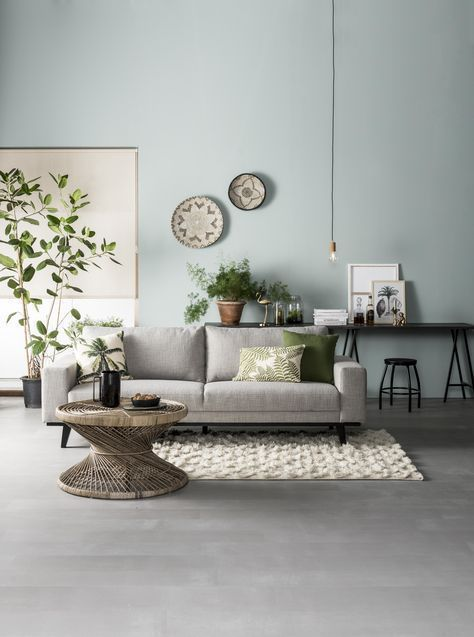 living room, grey wooden floor, blue wall, gey sofa, rattan coffee table,white rug, black table, black stool