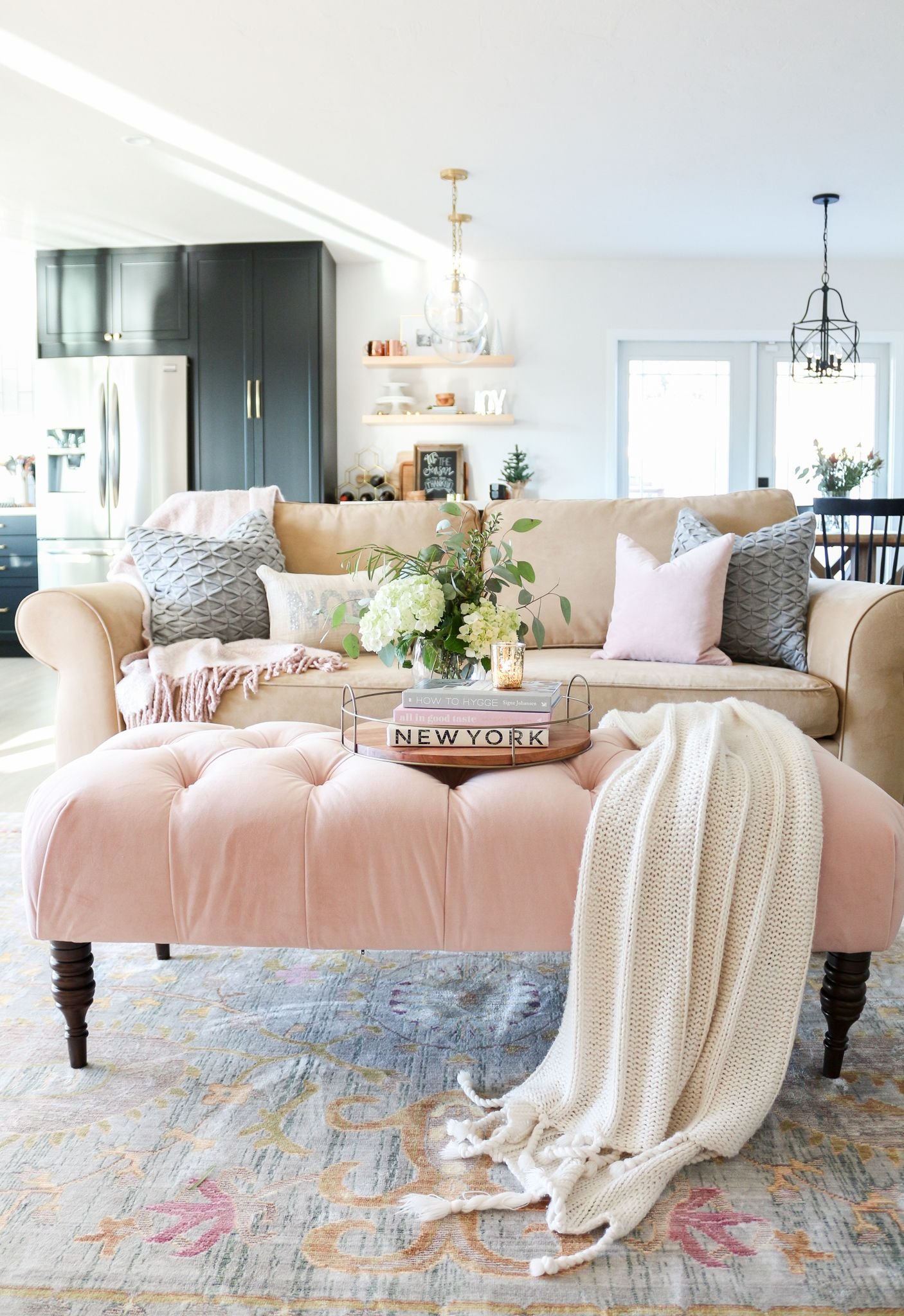 living room, patterned rug, brown sofa, pinnk tufted bench