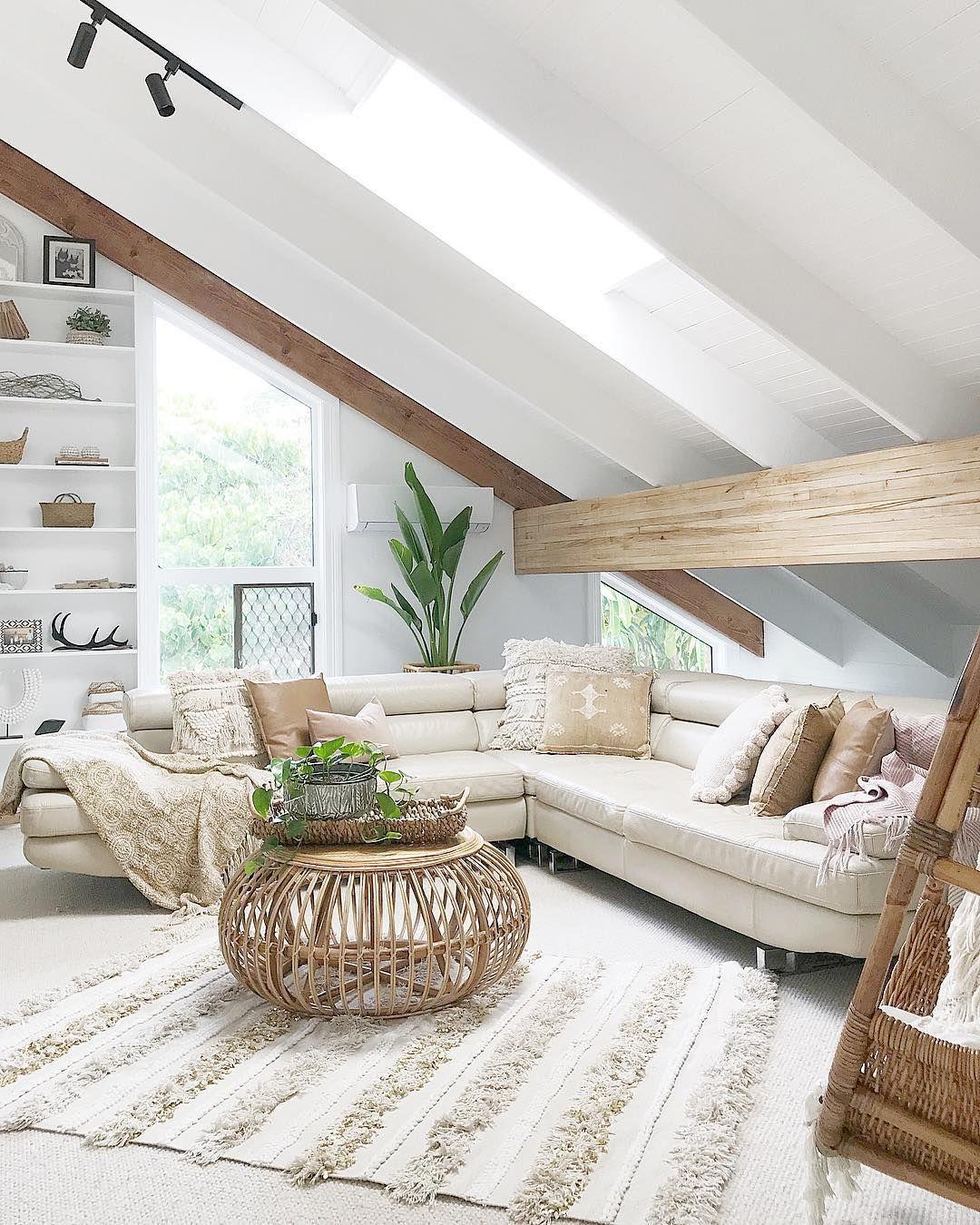living room, white floor, white vaulted ceiling, white corner sofa, rattan coffee table, white built in shelves