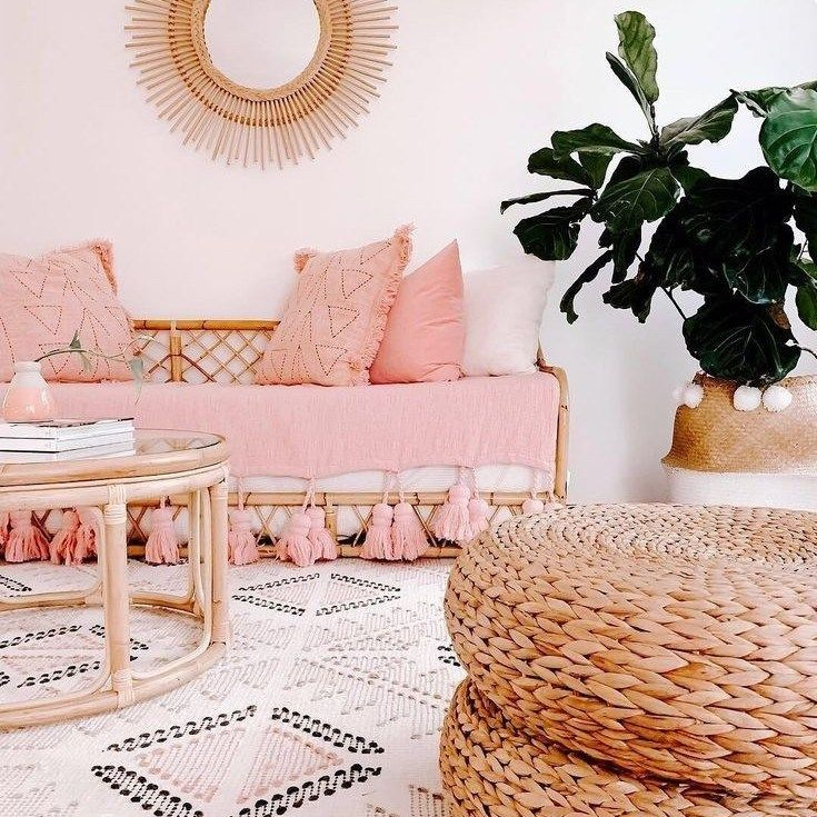 living room, white patterned rug, bamboo sofa with pink cushion, rattan coffee table, rattan ottoman