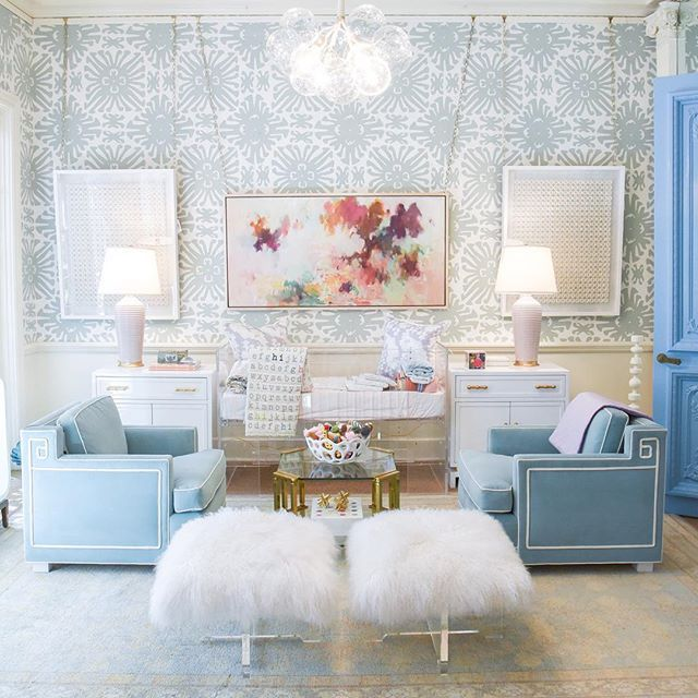 living room, white rug, blue patterned wall, blue sofa, glass coffee table, white fur stools, glass pendants, white cabinet