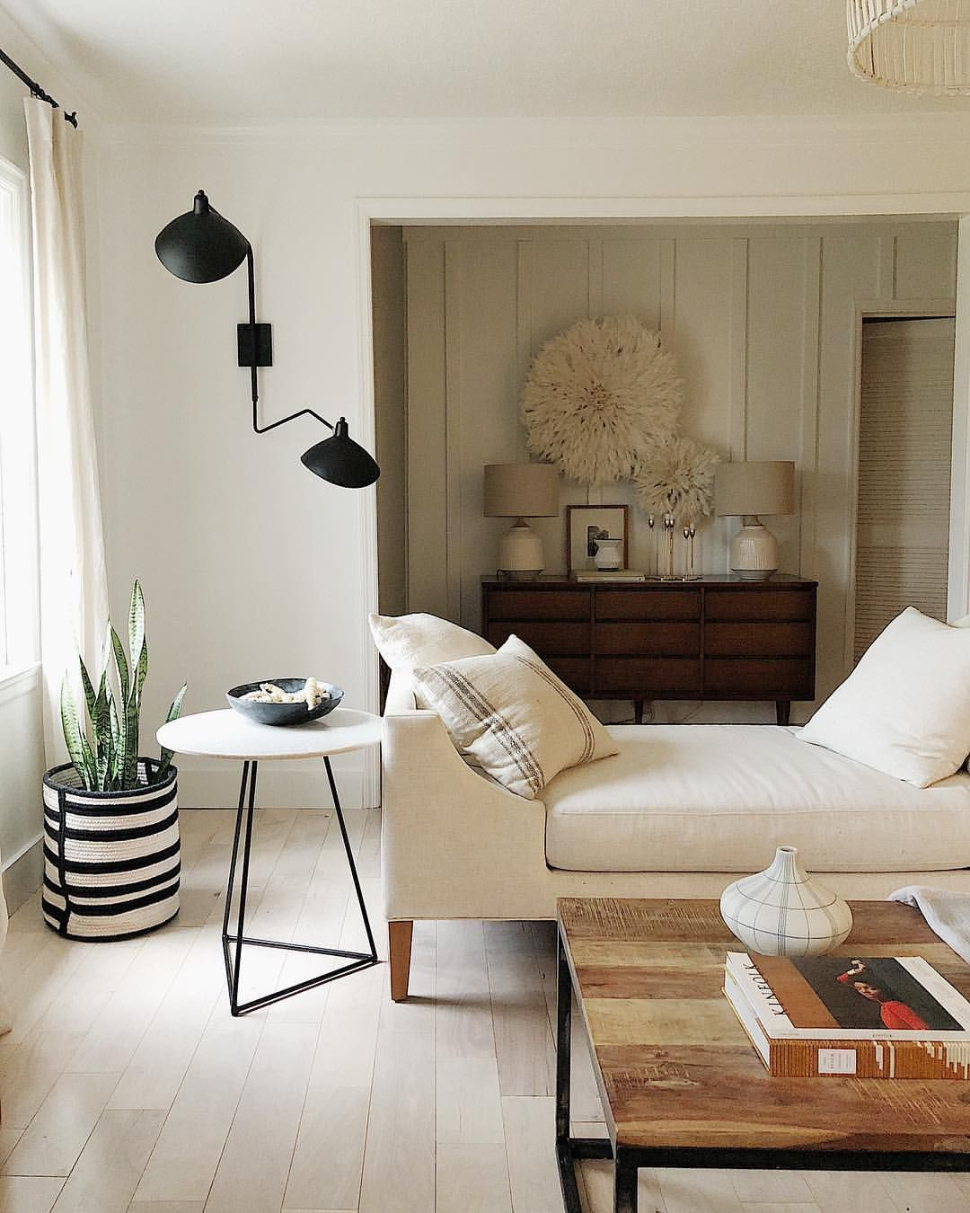 living room, white wall, white wooden floor, white sofa, white side table, wooden coffee table, black sconce