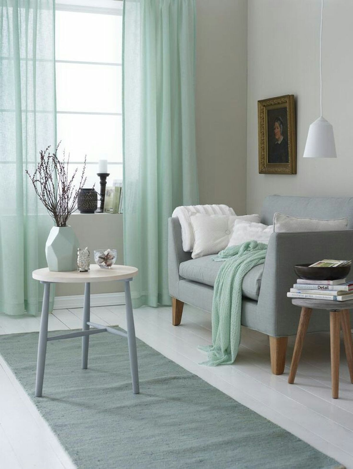 living room, white wooden floor, grey rug, green curtain, blue sofa, stools for table, white pendant
