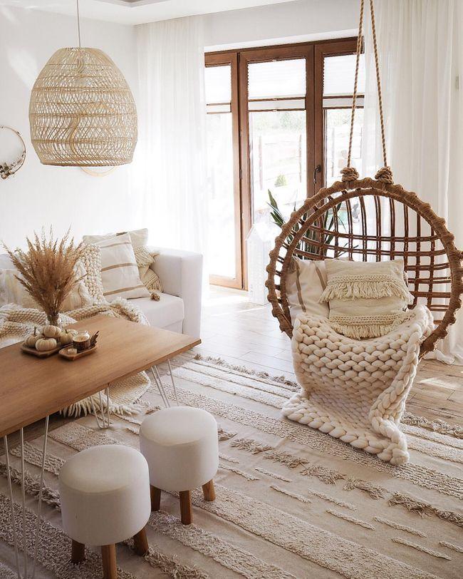living room, white wooden floor, white sofa, white sofa, wooden coffee table, rattan swing, white stools, rattan pendant
