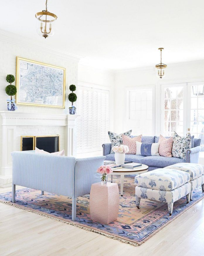 living room, white wooden floor, white wall, pendants, blue sofas, blue and white ottoman, round coffee table, white framed fireplace