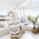 Living Room, White Wooden Floor, White Wall, White Tufted Corner Sofa, White Pillows, Wooden Round Coffee Table, Rattan Plant Pot
