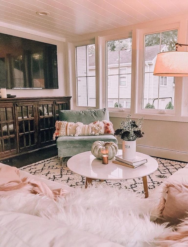 living room, wooden floor, patterned rug, white wall, green chair, white marble coffee table