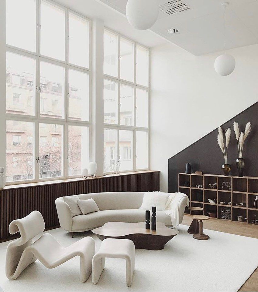 living room, wooden floor, white rug, white sofa, white chair, white ottoman, wooden coffee table, wooden shelves, large windows