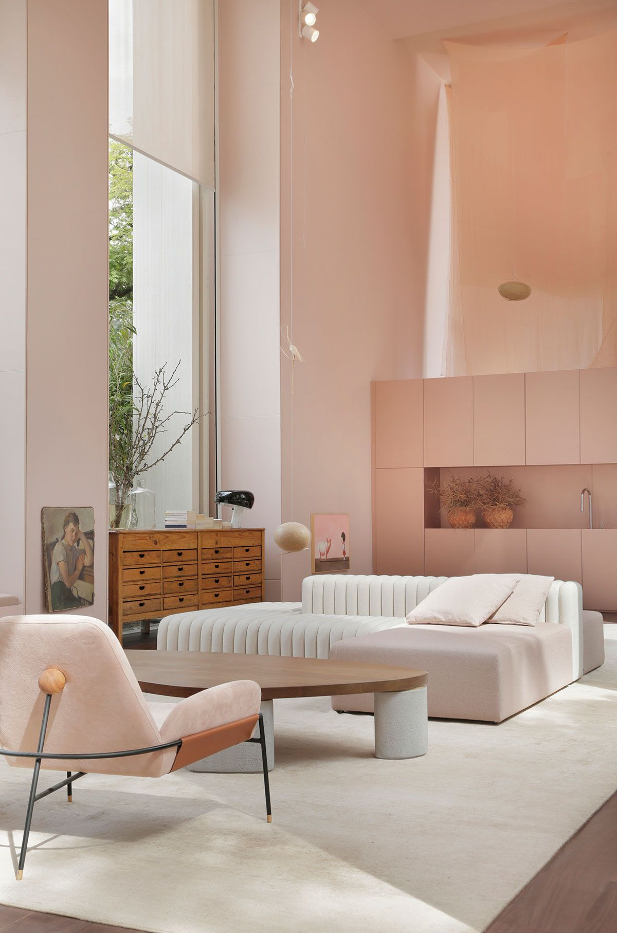 living room, wooden floor, white rug, white wall, pink cabinet, white sofa, wooden coffee table, pink chair