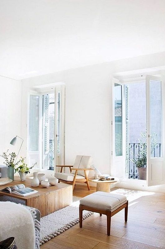 living room, wooden floor, white rug, wooden coffee table, wooden chair with white cushion, wooden stool with white cushion, tall door
