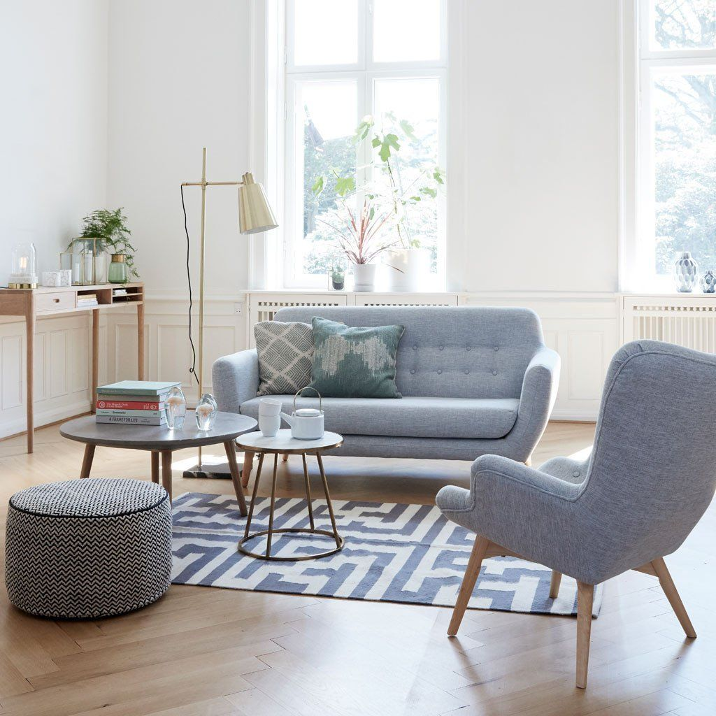 living room, wooden floor, white wall, wooden table, floor lamp, blue sofa, blue chair, round coffee tables
