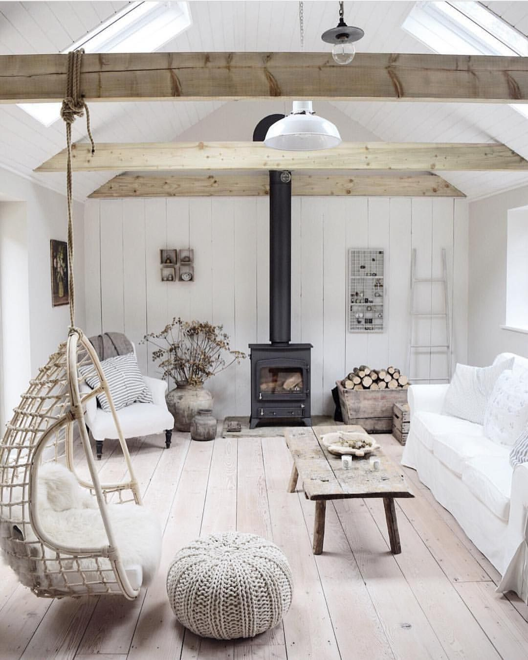 living room, wooden floor, wooden wall, rattan swing, wooden coffee table, white woven ottoman, wooden beams, shite sofa