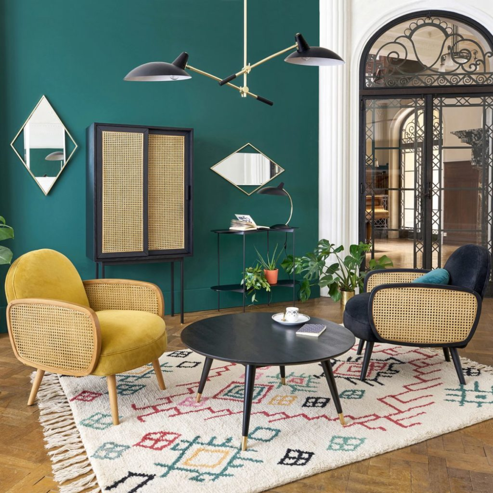 living room, wooden floor, yellow and black velvet chair with rattan armrest, green wall, black pendant, black round table, patterned rug