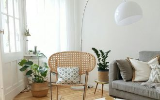living room, woodenf floor, white wall, white floor lamp, rattan rocking chair, grey sofa, geometrical coffee table, white rug
