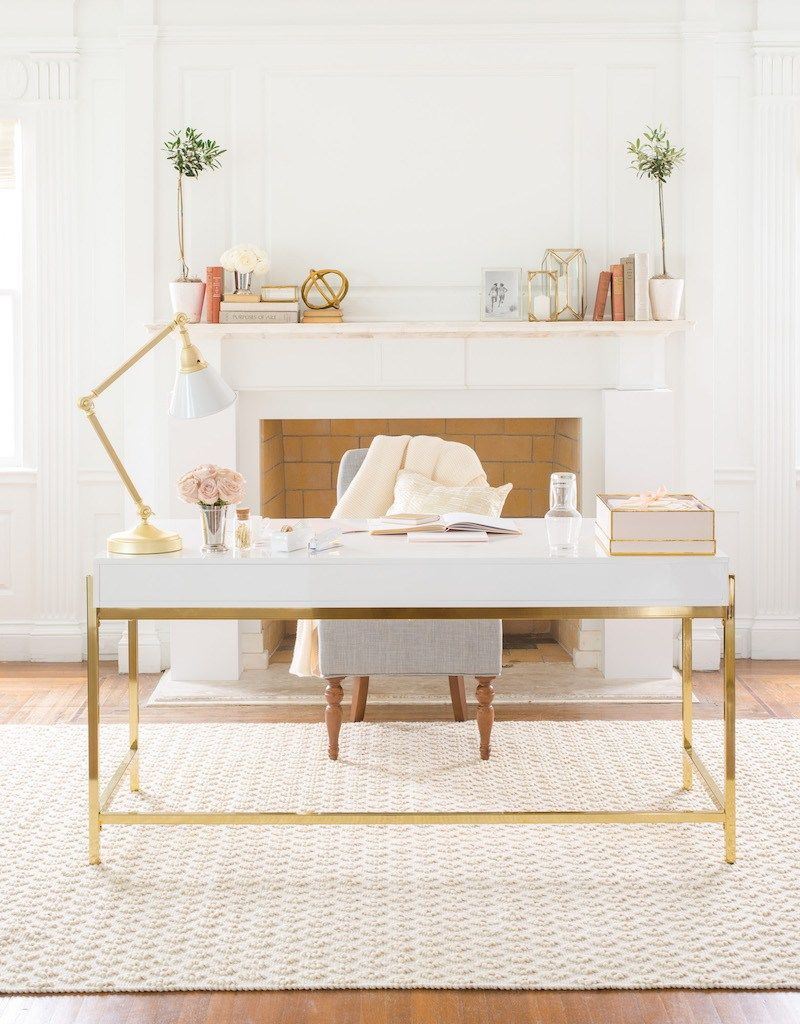 long white desk with golden lines, white chair, white rug, wooden floor, white wall, white gold table lamp