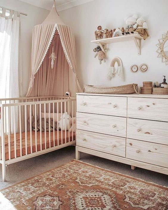 nursery, brown floor, brown patterned rug, white wall, wooden cabinet, wooden crib, pink canopy, wooden floating shelves