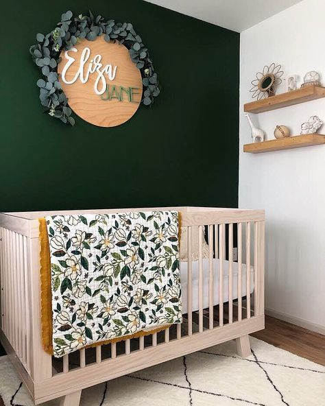 nursery, dark green accent wall, wooden round name plate, wooden crib, white wall, wooden floating shelves