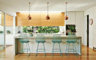 open kitchen, white cabinet, wooden upper cabinet, white island, green framed stool, copper pendants