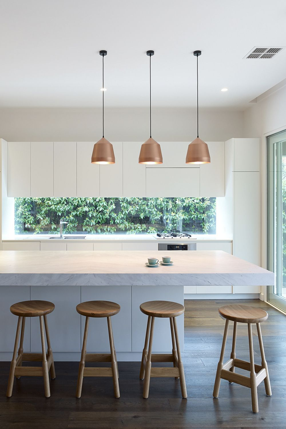 open kitchen, white upper cabinet, bottom cabinet, white island with white marble, wooden stools, copper pendants