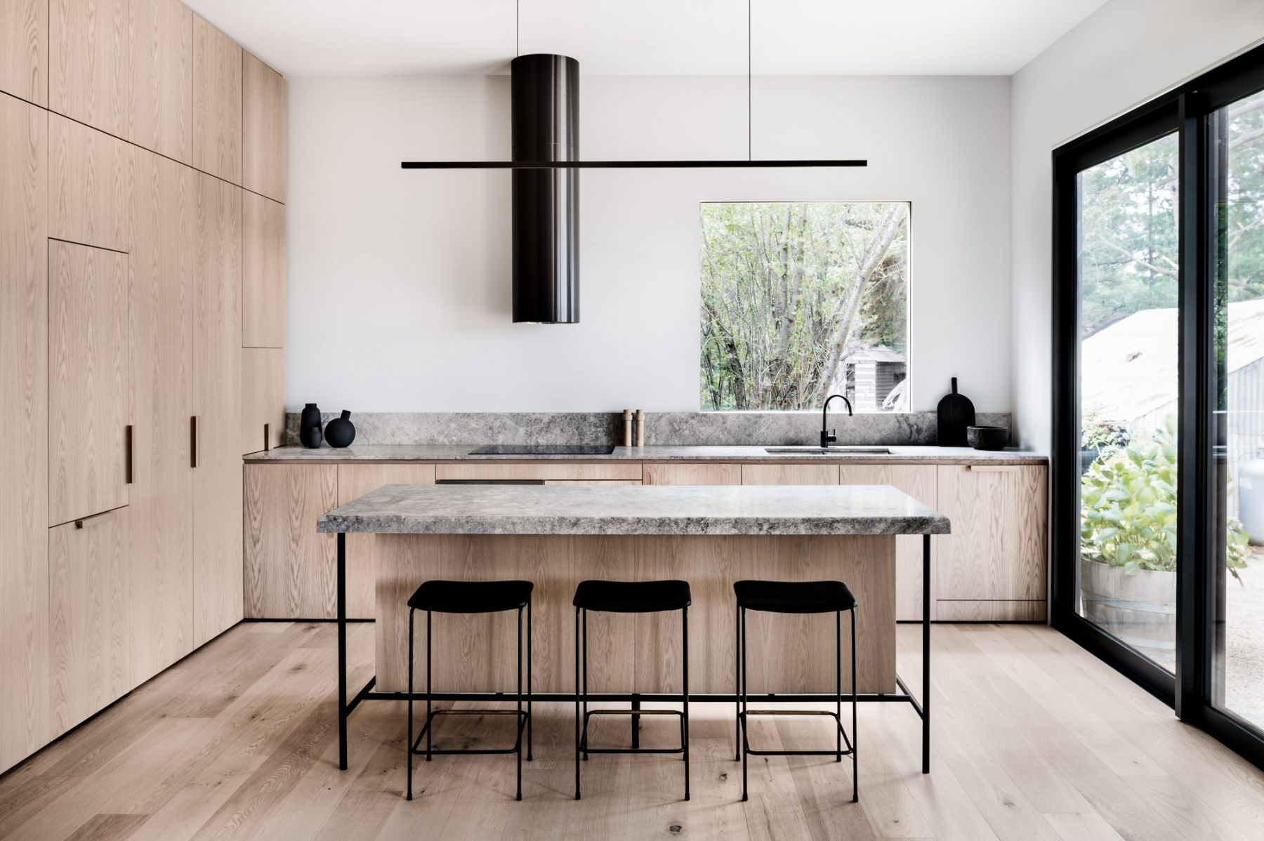 open kitchen, wooen cabinet wall, wooden bottom cabinet, black marble top, wooden island with black marble top
