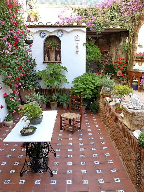 patio, brown floor tiles, white wall, flower, white table, brick wall