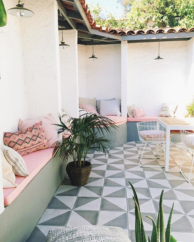 patio, white black floor tiles, white wall, built in bench with pink cushion, black pendants