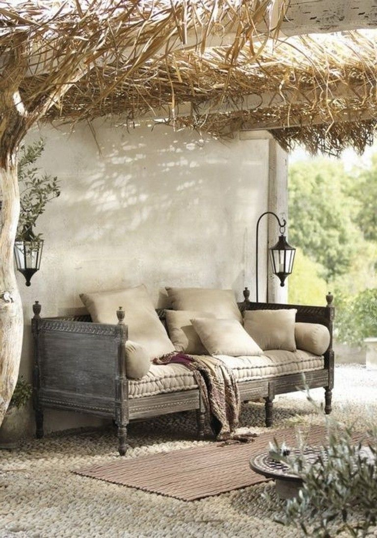 patio, white stones, white wall, black wooden sofa, rattan rug, black pendants, rattan ceiling