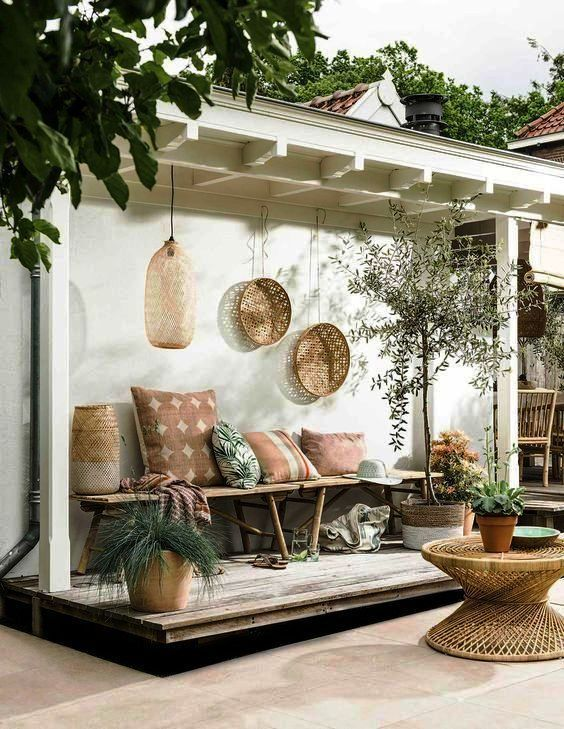 patio, wooden floor, white wall, white woodden roof, wooden benches, pillows, rattan pendant, rattan coffee table