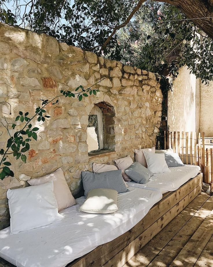 patio, wooden floor, wooden bench, stone wall, white cushion