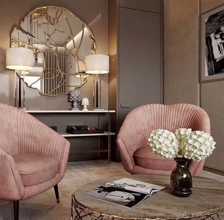 pink velvet chairs, marble round coffee table, round mirror with golden accents,