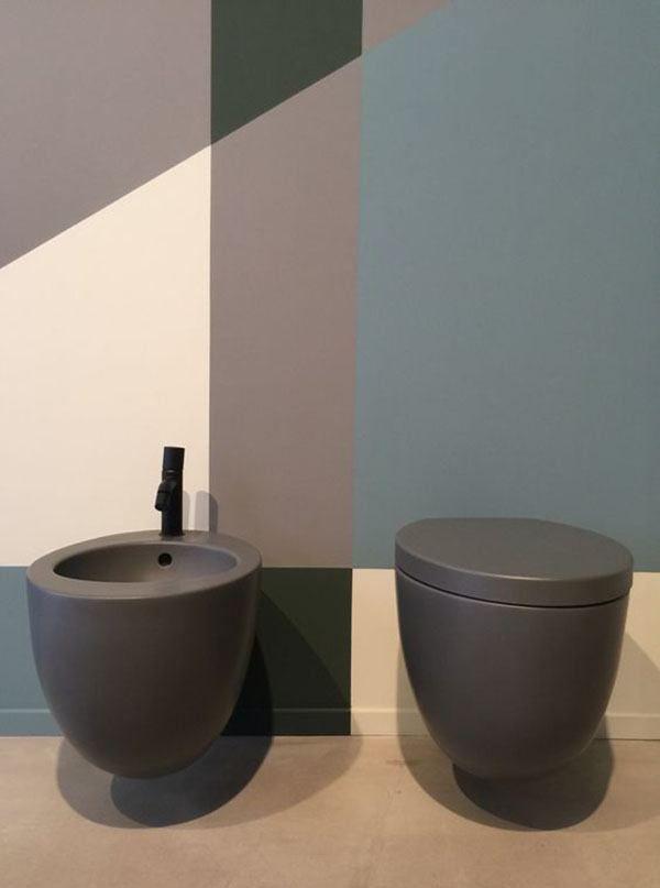 round dark grey toilet, dark grey sink with black faucet, blue pink brown wall
