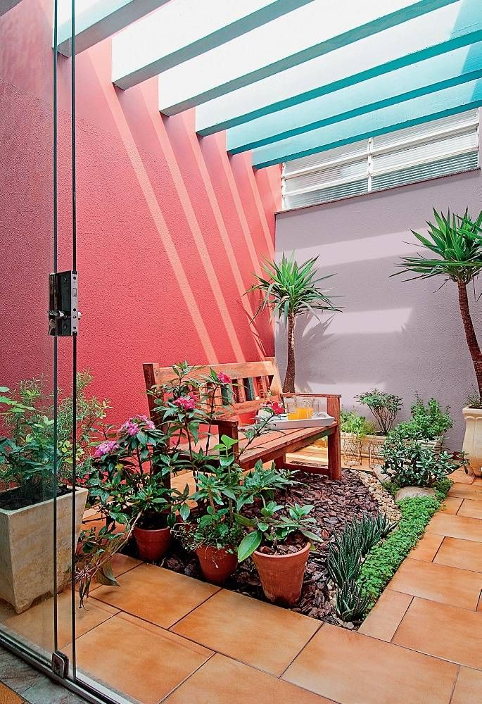 small garden, orage floor tiles, stones, pink wall, grey wall, wooden bench, plant pots, open ceiling, glass sliding glass