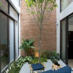 Small Garden, Plants Along The Wall, Red Brick Wall, White Brick Wall, Wooden Side Table, Wooden Lounge Chair With Blue Cushion, Tree